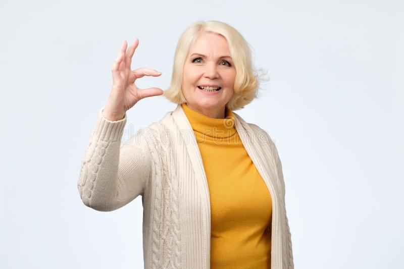 Senior woman showing small size sign with fingers stock photo