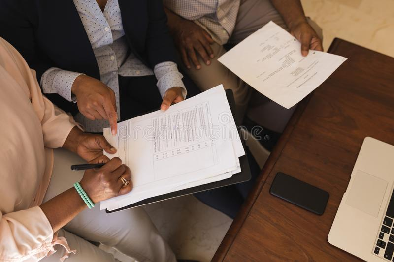 Senior woman signing property contract with real estate agent. Overhead view of a senior African American woman signing property contract with real estate agent royalty free stock photography
