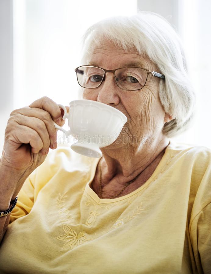 Senior woman sipping tea while looking at the camera royalty free stock photo