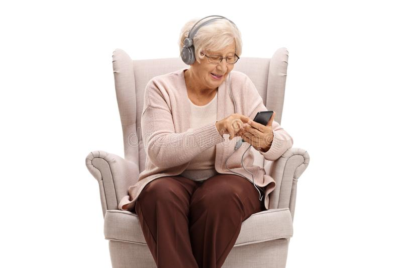 Senior woman sitting in an armchair and listening to music on a phone. On white background stock photos