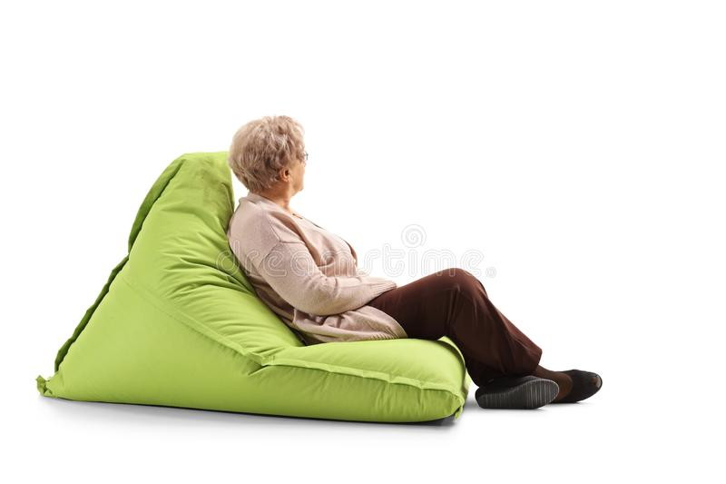 Senior woman sitting on a bean bag and looking away. Full length profile shot of a senior woman sitting on a bean bag and looking away isolated on white stock photography