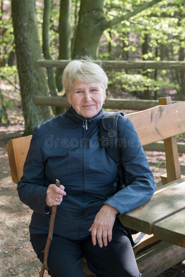 Senior woman sitting on a bench stock photography
