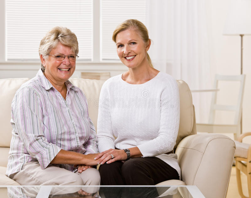 Senior woman sitting with daughter in livingroom stock photo