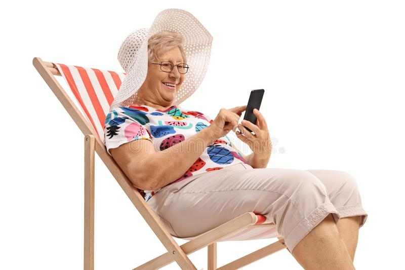 Senior woman sitting in a deck chair and looking at a phone. Isolated on white background stock photos