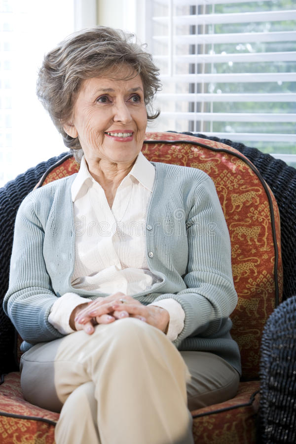 Senior woman sitting on living room chair. Smiling stock photography