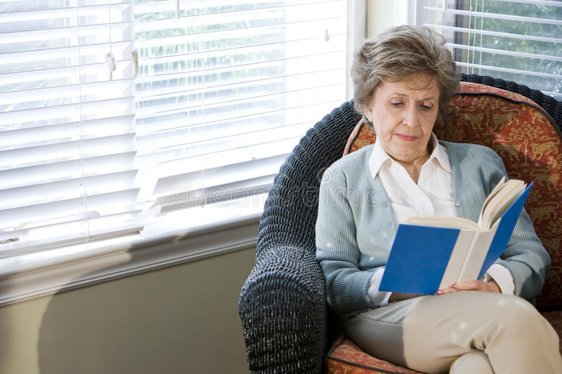 Senior woman sitting on living room chair reading. Book royalty free stock photography