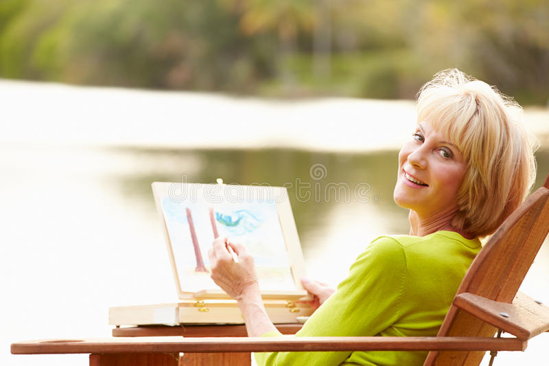 Senior Woman Sitting At Outdoor Table Painting Landscape stock photo