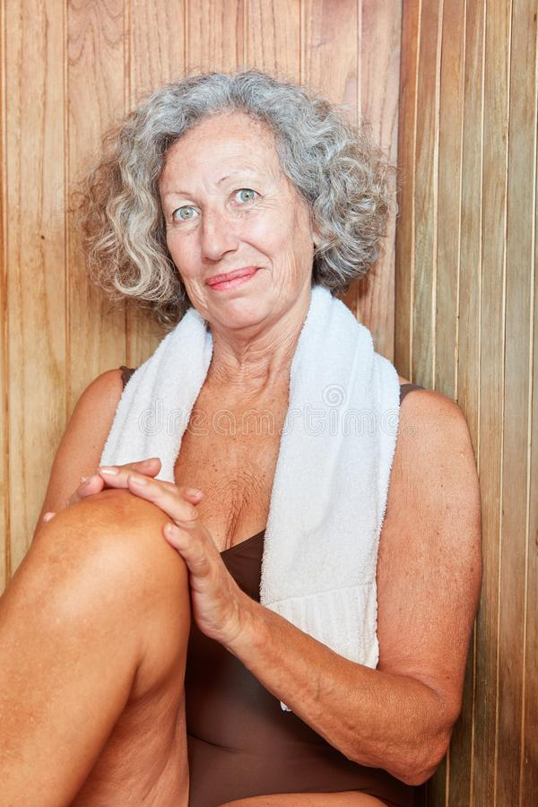 Senior woman in the sauna is doing wellness. Senior woman sitting smiling and relaxing in the sauna at the Wellness Hotel stock photo