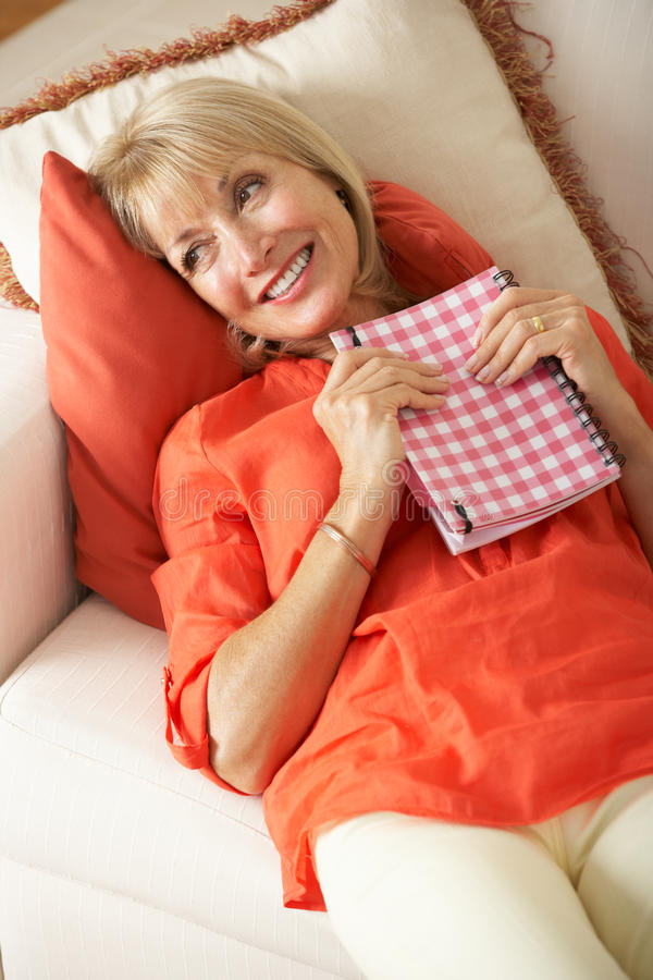 Download Senior Woman Sitting On Sofa Reading Diary Stock Image - Image: 26614867