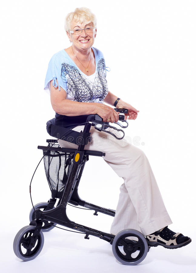 Senior woman sitting on walker. Smiling senior woman with happy expression in face is sitting on a modern walker for handicapped people isolated on white stock photography