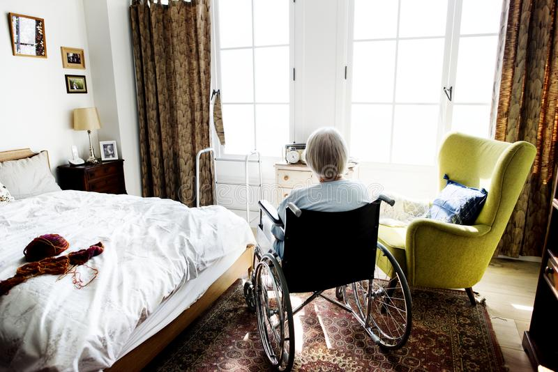 Senior woman sitting on the wheelchair alone royalty free stock images