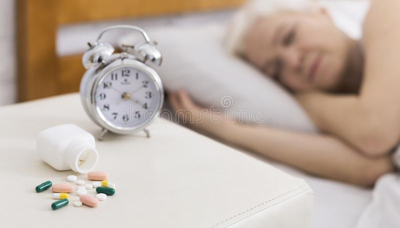 Senior woman sleeping in bed with help of pills royalty free stock photos
