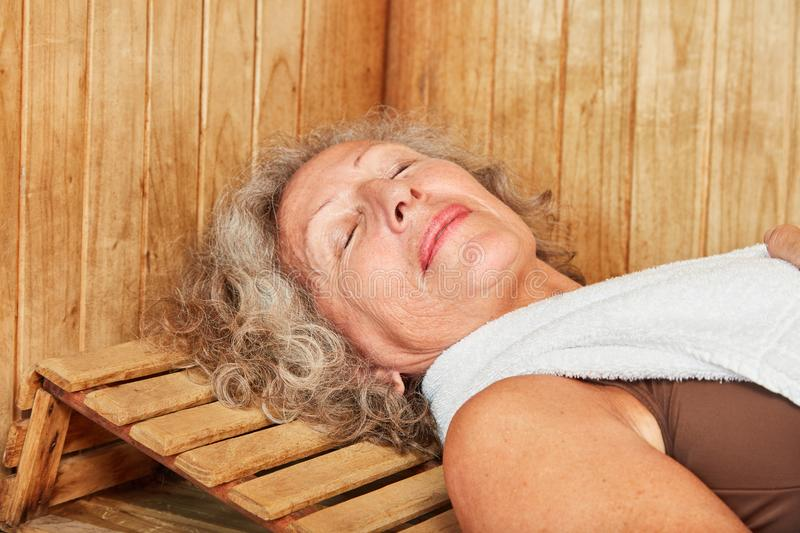 Senior woman sleeps in the wellness sauna. And enjoys the healthy heat royalty free stock images
