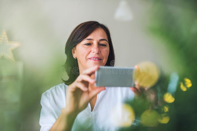 A senior woman with smartphone by a Christmas tree at home, taking selfie. stock photography