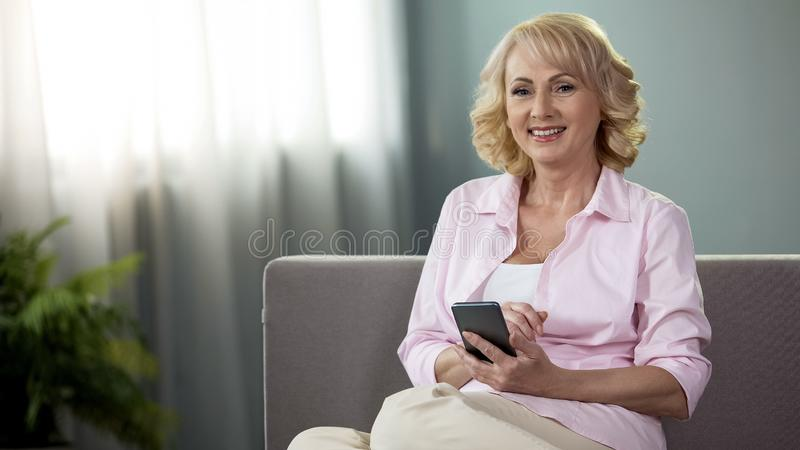 Senior woman with smartphone smiling in camera, online banking, financial app royalty free stock image