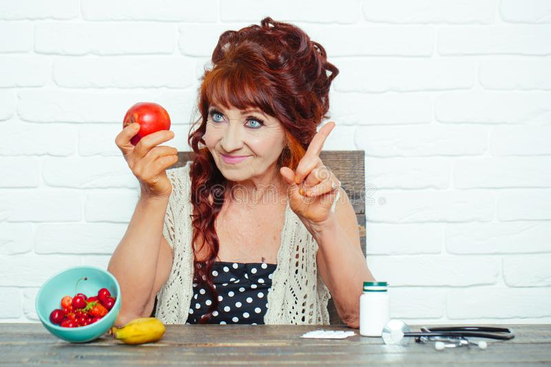 Senior woman smile with apple in hand royalty free stock photos
