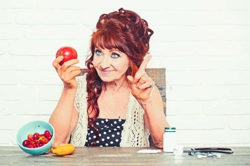 Senior woman smile with apple in hand stock images