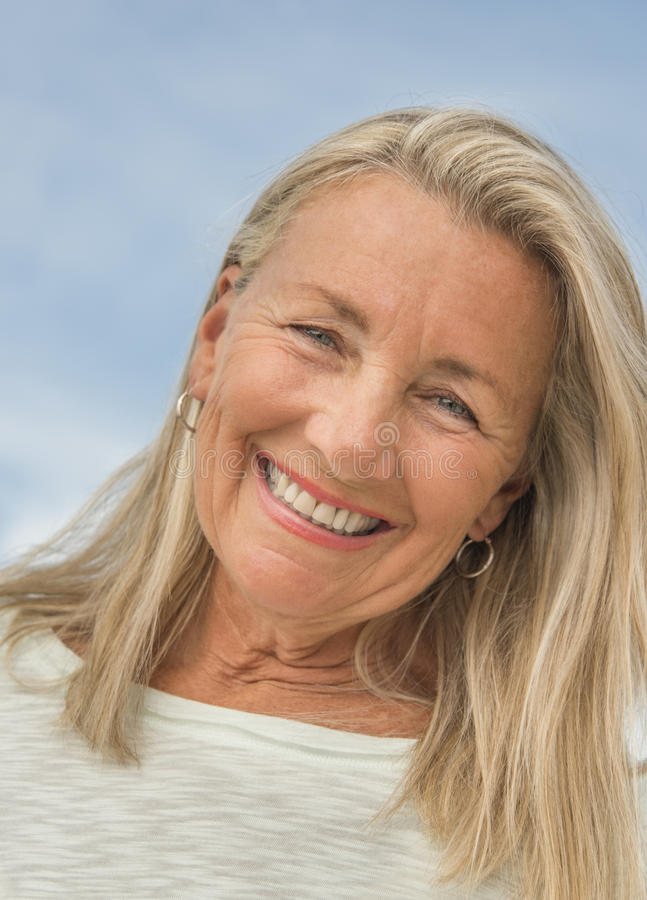 Senior Woman Smiling Against Sky stock images