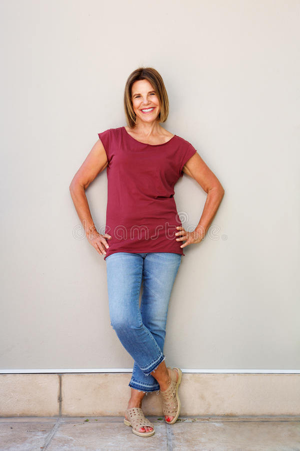Senior woman smiling against wall royalty free stock image