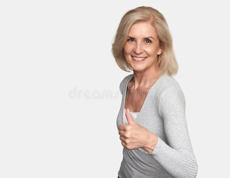 Old lady making thumb up sign stock image