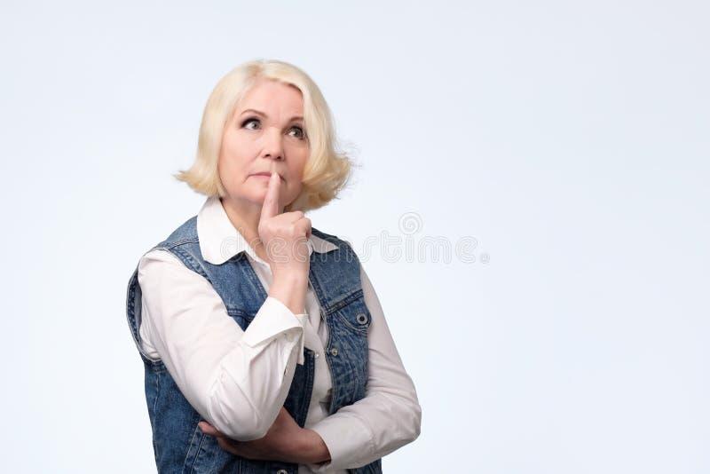 Senior woman smirking thinking trying create plan in mind royalty free stock image
