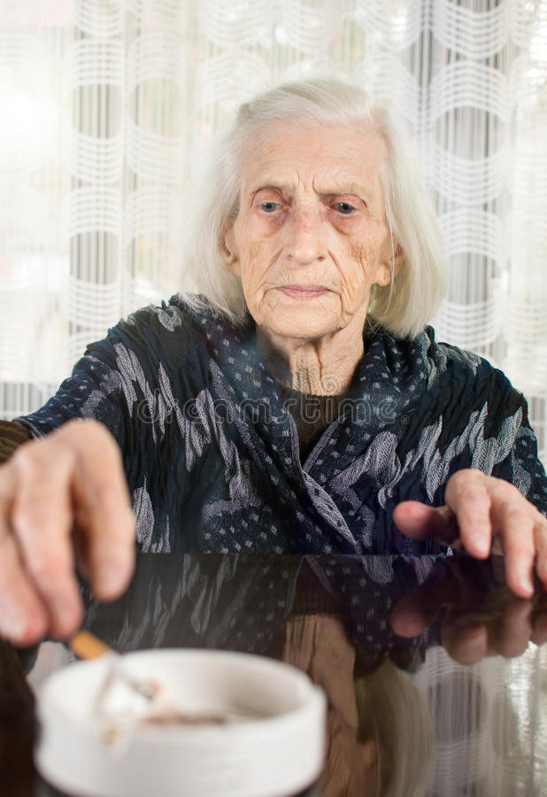 Senior woman smoking a cigarette. At home stock image