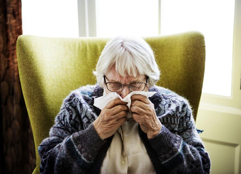 Senior woman sneezing on couch stock image