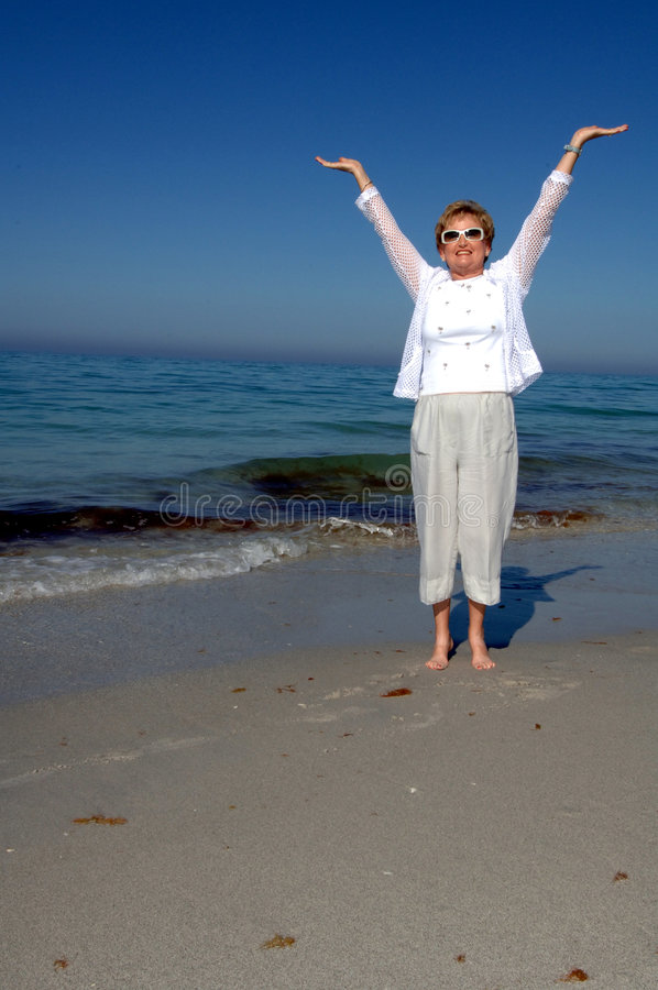 Senior woman soaking up sun. A senior woman wearing sunglasses on the beach with arms stretched out to sky royalty free stock photo