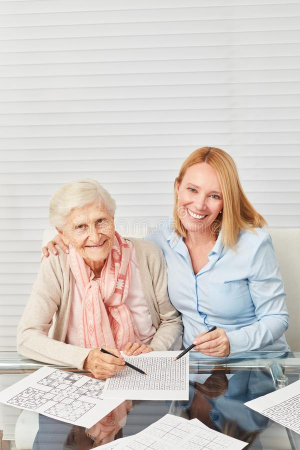 Senior woman solves puzzles together with daughter stock images