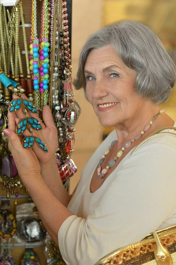 Senior woman at souvenir store. Portrait of beautiful senior woman at souvenir store royalty free stock image
