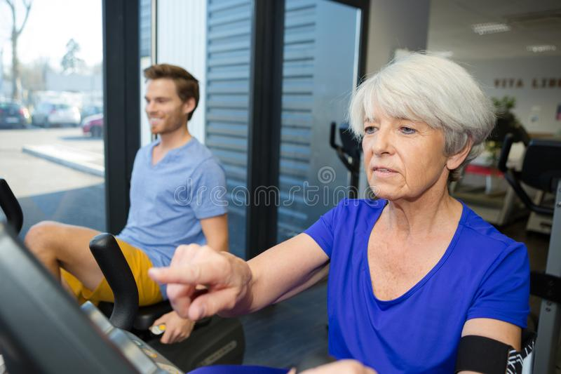 Senior woman spinning on fitness bikes with personal trainer royalty free stock images