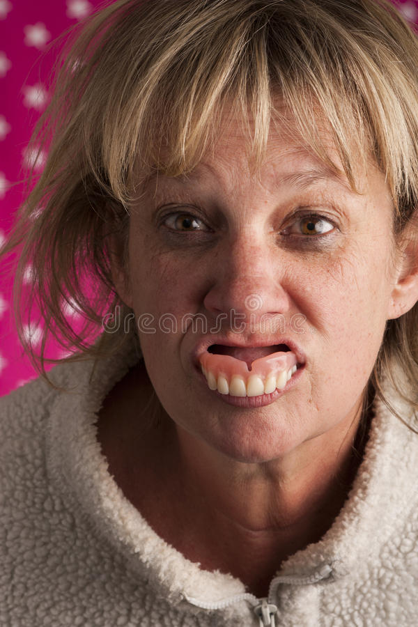 Senior woman spitting out teeth stock image
