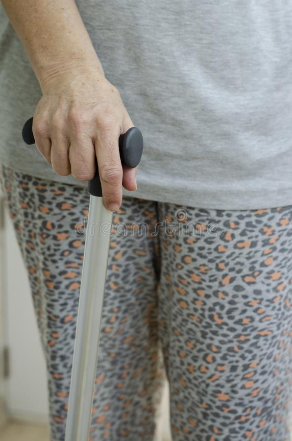 Senior woman standing with her hands on the handles of a walking cane. Rehabilitation and healthcare concept. Vertical stock photo