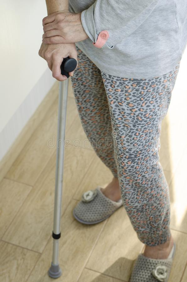 Senior woman standing with her hands on the handles of a walking cane. Rehabilitation and healthcare concept. Vertical royalty free stock photo