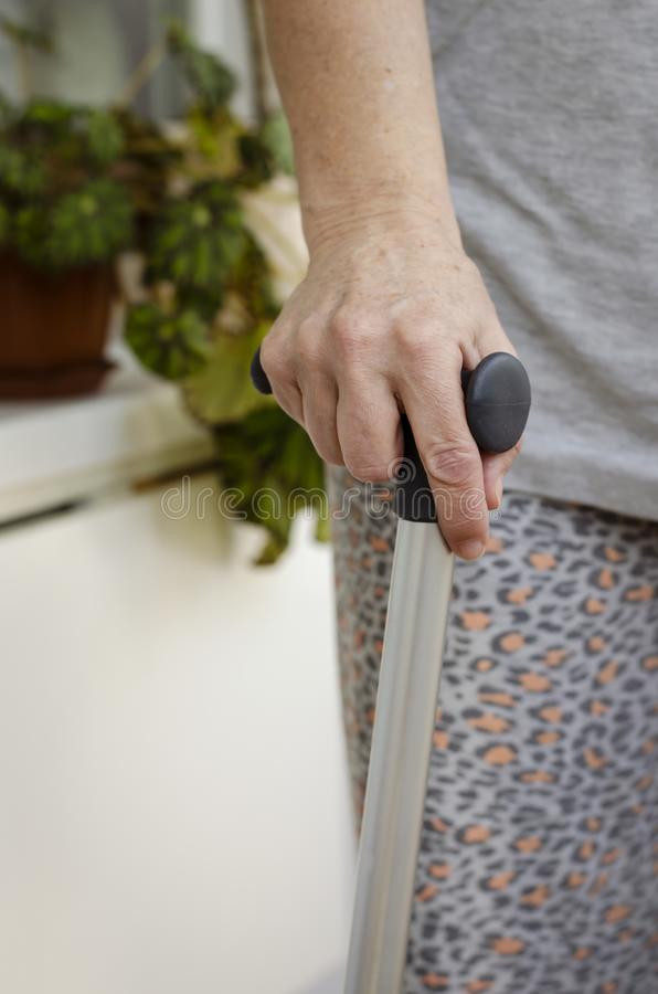 Senior woman standing with her hands on the handles of a walking cane. Rehabilitation and healthcare concept. Vertical stock image