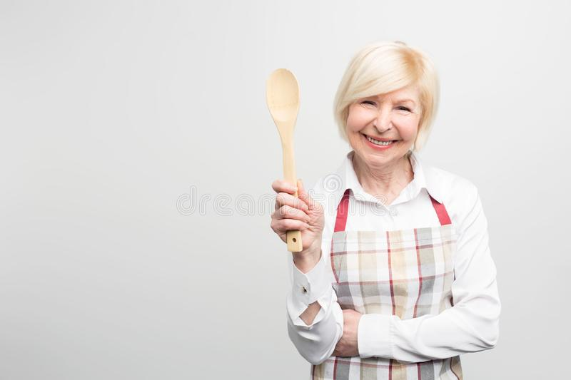 Senior woman standing and holding a spoon. She is a good housewife. She likes to cook tasty food. Isolated on white royalty free stock image