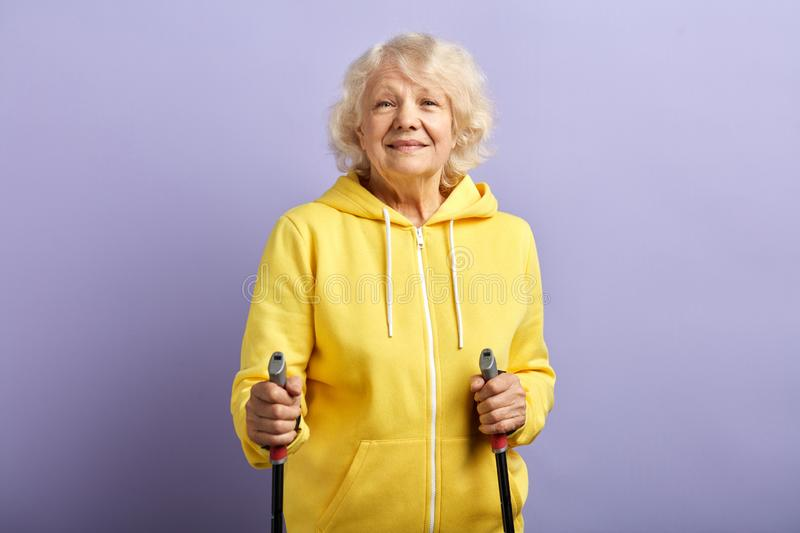 Senior woman standing with Nordic walking poles in violet studio. royalty free stock image