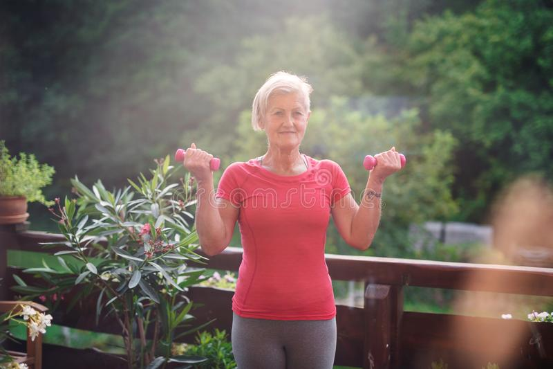 A senior woman standing outdoors on a terrace in summer, doing exercise. royalty free stock images