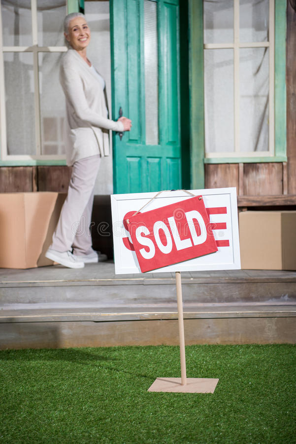 Senior woman standing on porch of new house with sold sign stock photography