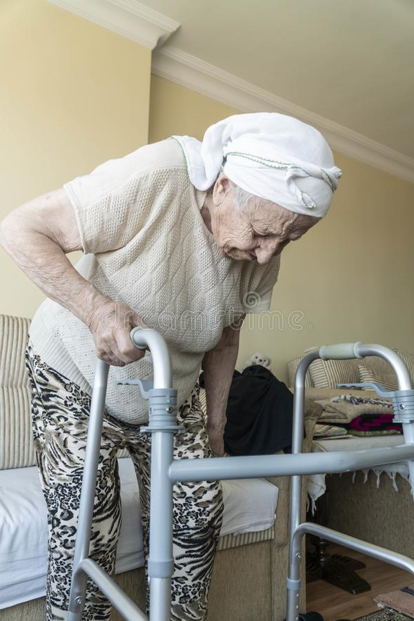 A senior woman standing up with a walker in home stock photography