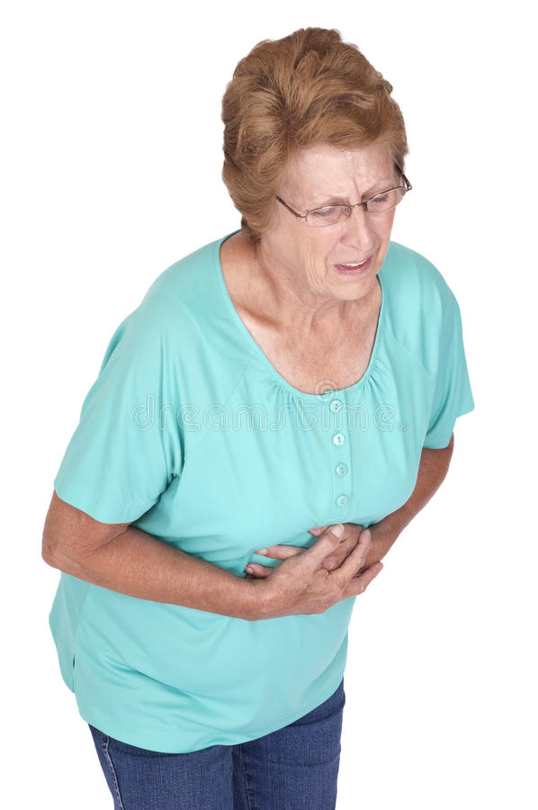 Senior Woman Stomach Ache Heartburn Pain Isolated. Mature senior woman suffers from intestinal pain or an old fashioned tummy ache or gas. The lady has pain or stock photo
