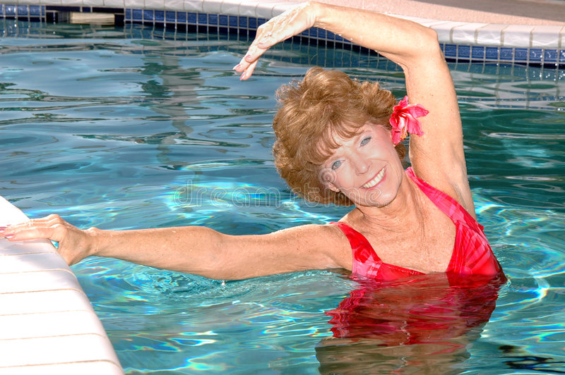 Senior woman stretching in the pool. An attractive smiling senior woman stretching by the edge of the pool stock photo
