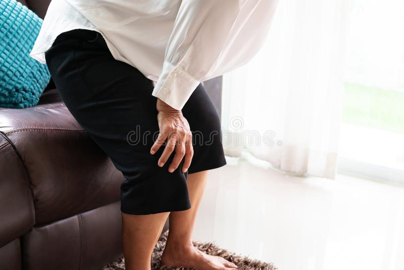 Senior woman suffering from knee pain at home, health problem concept royalty free stock photo