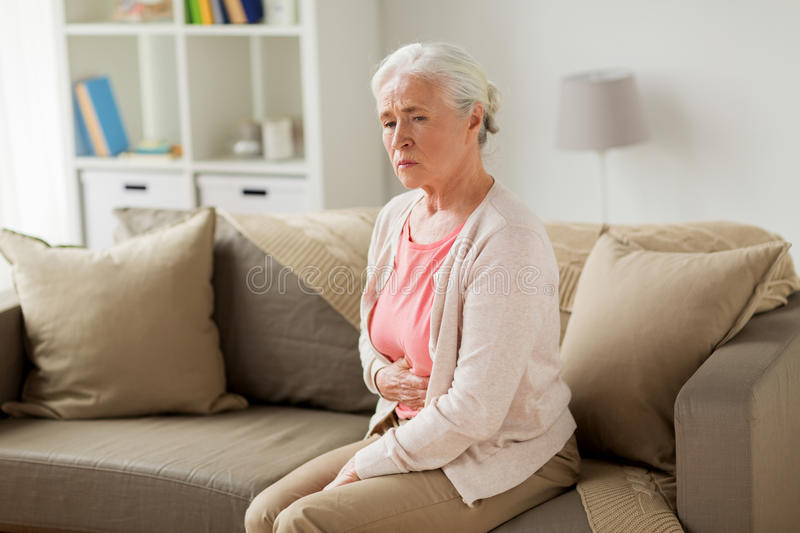 Senior woman suffering from stomach ache at home stock photos