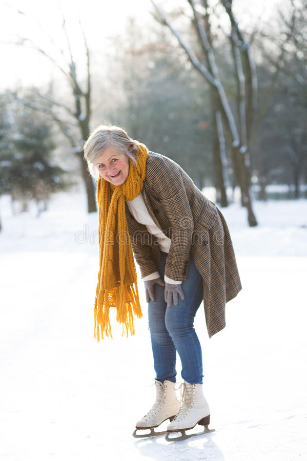 Senior woman in sunny winter nature ice skating. stock photography