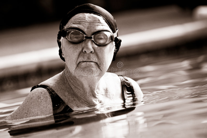 Senior Woman Swimming in a pool stock images