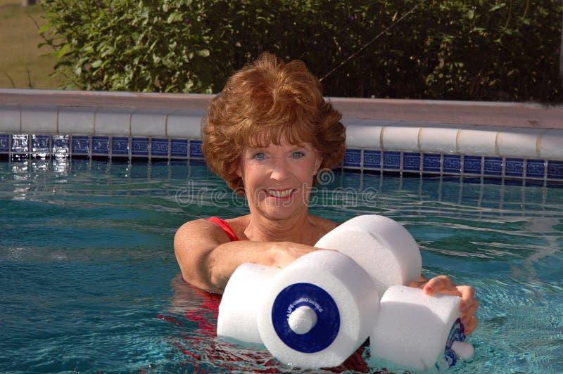 Senior woman swimming pool exercises. An attractive smiling senior woman doing exercises in the pool royalty free stock photo