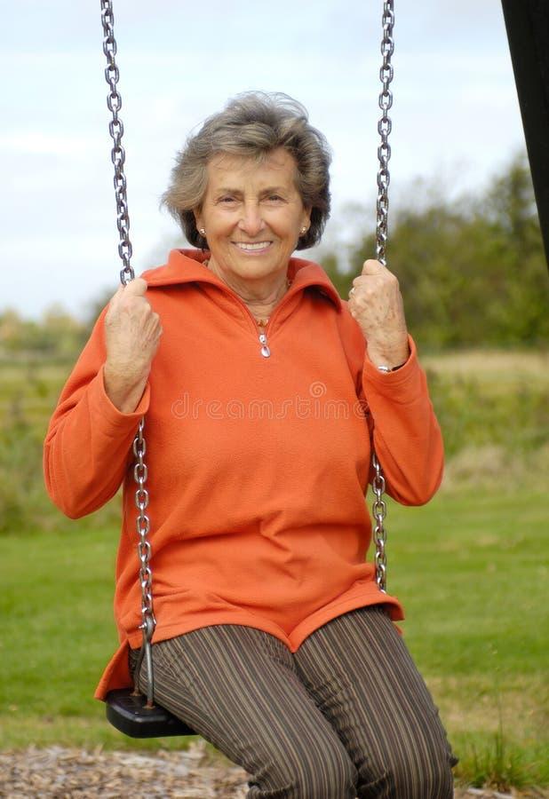 Senior woman on a swinger stock photography