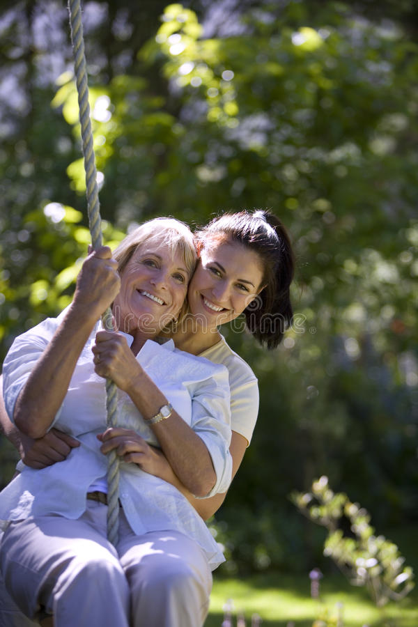 Senior woman swinging on garden rope swing, adult daughter embracing her, smiling, front view, portrait royalty free stock photos