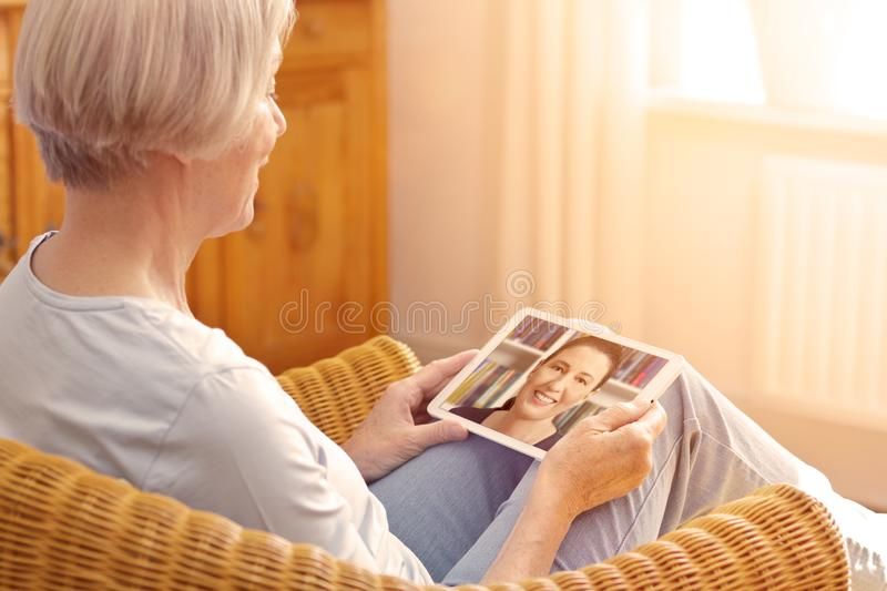 Senior woman tablet computer granddaughter stock photo